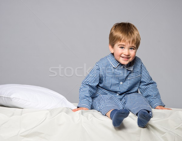 Playful little boy wearing blue pyjamas in bed Stock photo © Nejron