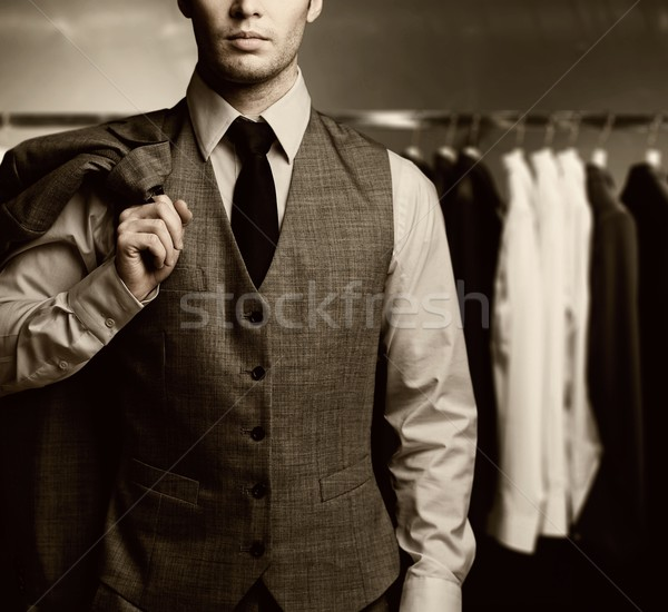 Stock photo: Businessman in classic vest against row of suits in shop
