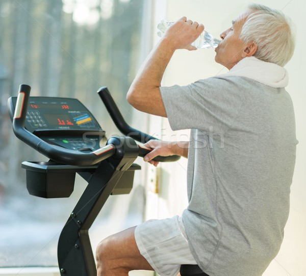 Senior man drinking while doing exercise on a bike in a fitness club Stock photo © Nejron