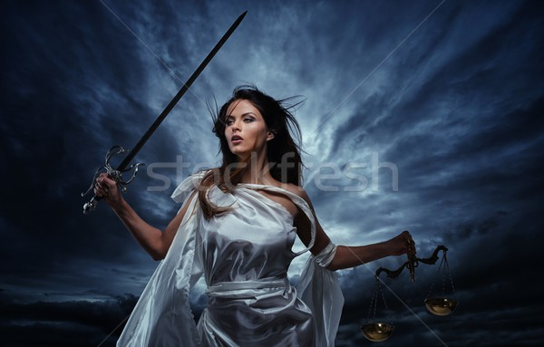 Femida, Goddess of Justice, with scales and sword against dramatic stormy sky Stock photo © Nejron