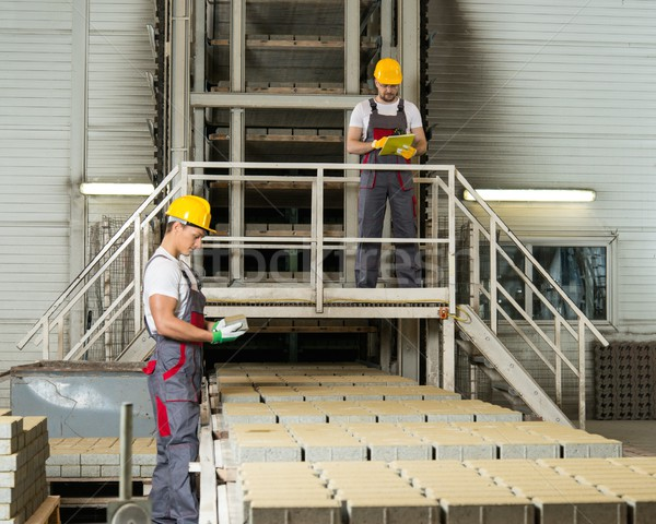 Worker and foreman in a safety hats on a factory   Stock photo © Nejron
