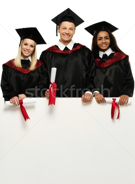 Multi ethnic group of graduated young students with blank notice board Stock photo © Nejron