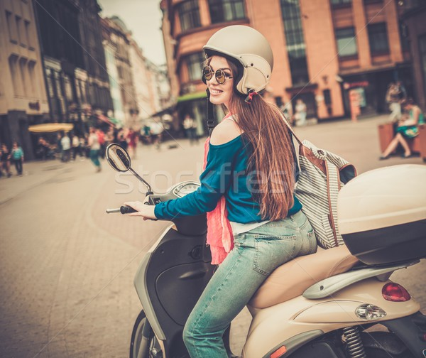 Young cheerful girl driving scooter in in european city  Stock photo © Nejron