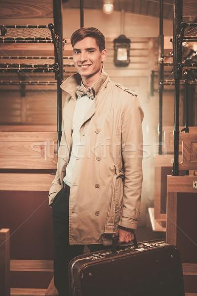 élégant jeune homme valise manteau à l'intérieur vintage Photo stock © Nejron
