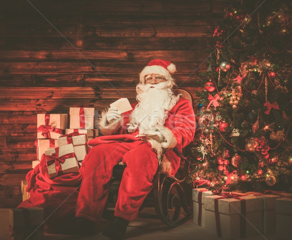 Santa Claus sitting on rocking chair in wooden home interior with letters in hands Stock photo © Nejron