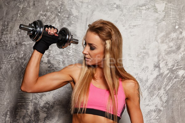 Sporty woman with dumbbell on grey concrete background  Stock photo © Nejron