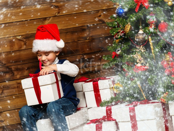 Little boy opening gift box under christmas tree in wooden house interior  Stock photo © Nejron