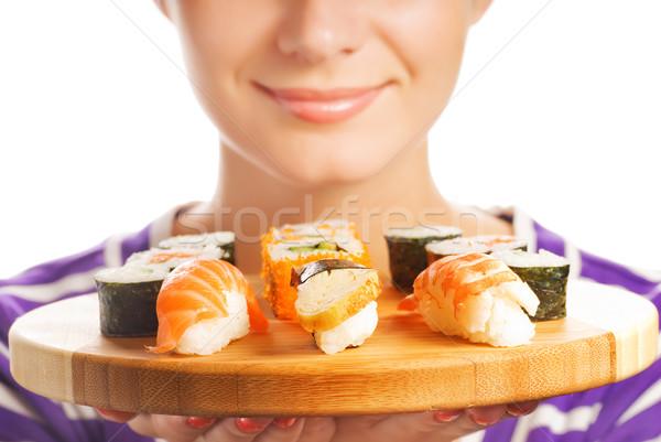 Happy woman holding bamboo plate with fresh sushi set on it (Sha Stock photo © Nejron