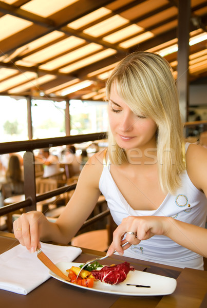 Beautiful young woman eating vegetarian food in a restaurant Stock photo © Nejron