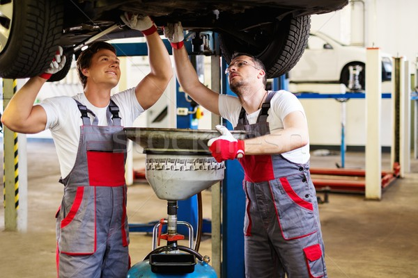 Two mechanic changing oil  in a car workshop Stock photo © Nejron