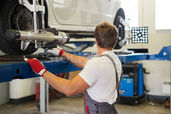 Young serviceman checking wheel alignment  in a car workshop  Stock photo © Nejron
