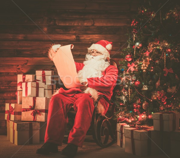 Santa Claus in wooden home interior reading wish list scroll Stock photo © Nejron