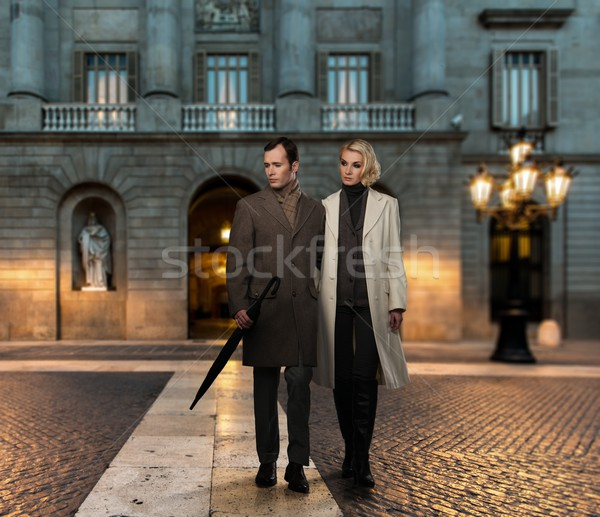 Elegant couple in coats against building facade in evening Stock photo © Nejron