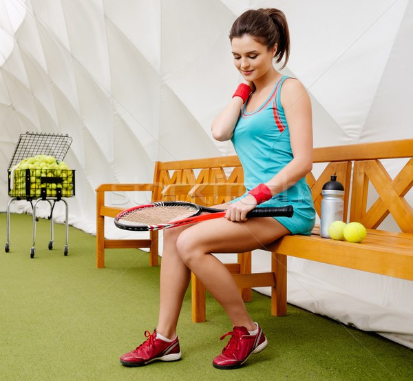 Stock photo: Young woman resting on a bench after tennis workout