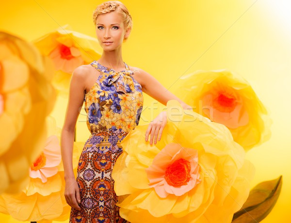 Beautiful young blond woman in colourful dress among big yellow flowers Stock photo © Nejron