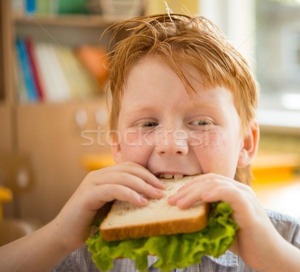 Little redhead schoolboy eating sandwich in class Stock photo © Nejron