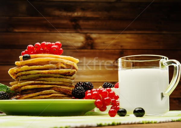 Healthy breakfast with pancakes, fresh berries and milk on tablecloth in rural interior  Stock photo © Nejron