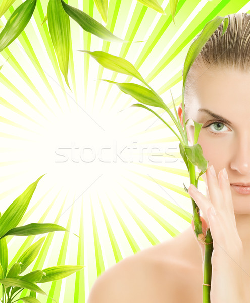 Beautiful young woman with bamboo plant over abstract green back Stock photo © Nejron