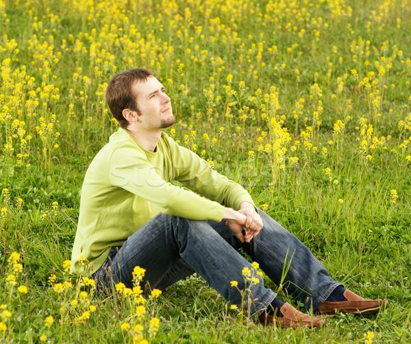 Jeune homme séance champ de fleurs printemps herbe Photo stock © Nejron