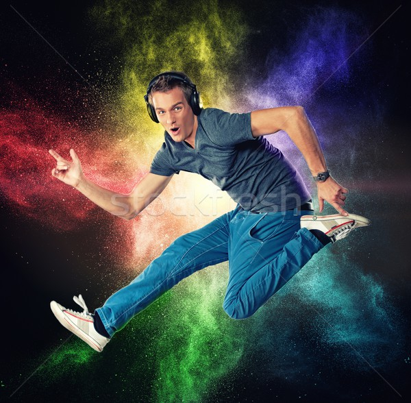 Handsome man with headphones jumping against colourful powder explosion  Stock photo © Nejron