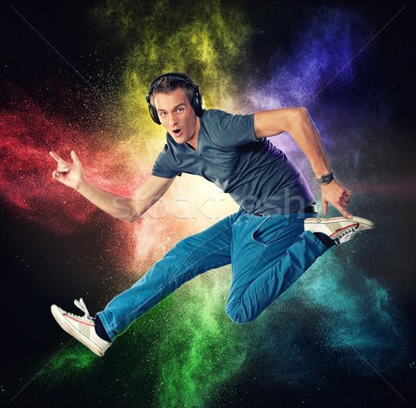 Hombre guapo auriculares saltar colorido polvo explosión Foto stock © Nejron