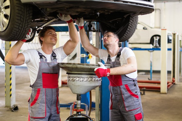 Two mechanics changing oil  in a car workshop Stock photo © Nejron