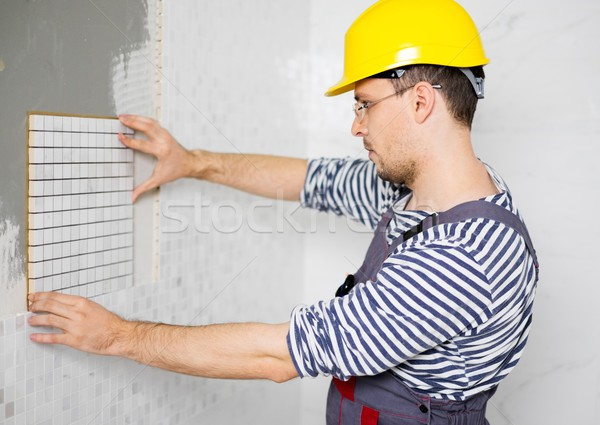 Builder applying tile on a wall Stock photo © Nejron