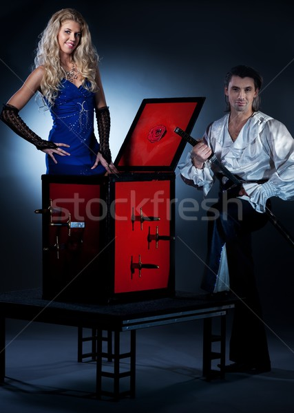 Attractive couple performing sword box illusion Stock photo © Nejron