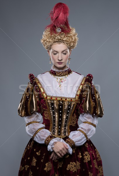 Stock photo: Haughty queen in royal dress isolated on grey
