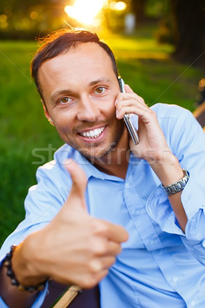 Happy handsome middle-aged man with mobile phone outdoors  Stock photo © Nejron