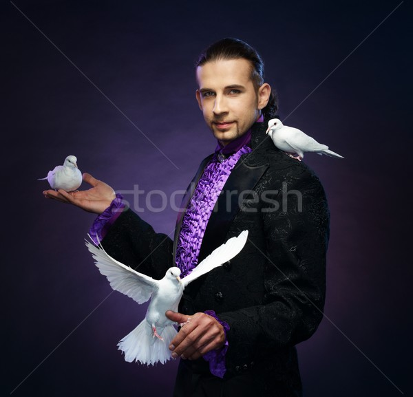 Young handsome brunette magician man in stage costume with his trained white doves Stock photo © Nejron