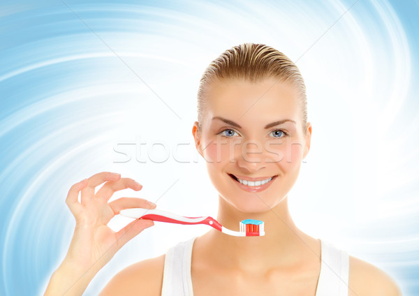 Young beautiful woman with a toothbrush over abstract blue backg Stock photo © Nejron
