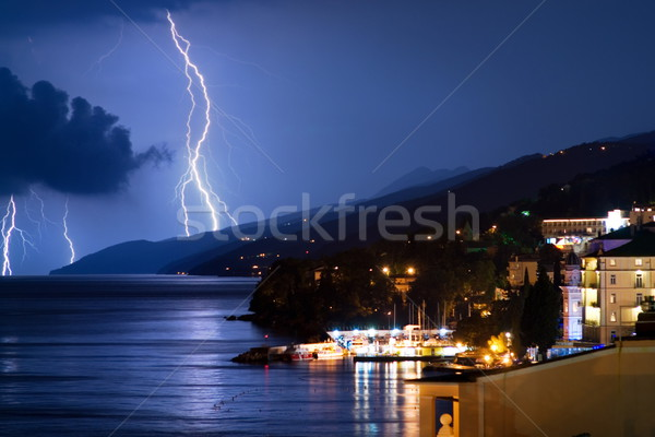 Small city near the ocean at stormy night Stock photo © Nejron