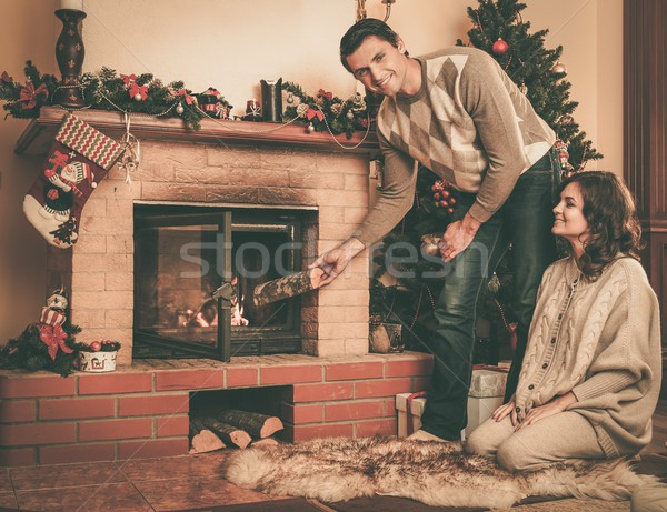 Couple putting log into  fireplace in Christmas decorated house interior  Stock photo © Nejron