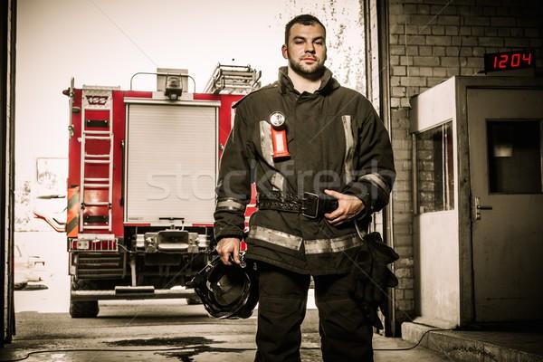 Firefighter against truck in firefighting depot  Stock photo © Nejron