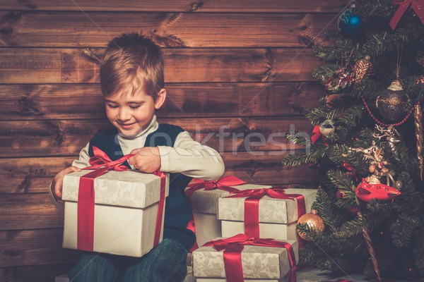 Little boy with gift box under christmas tree in wooden house interior  Stock photo © Nejron