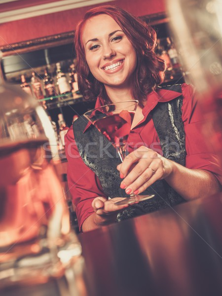Beautiful redhead barmaid with cocktail behind bar counter Stock photo © Nejron