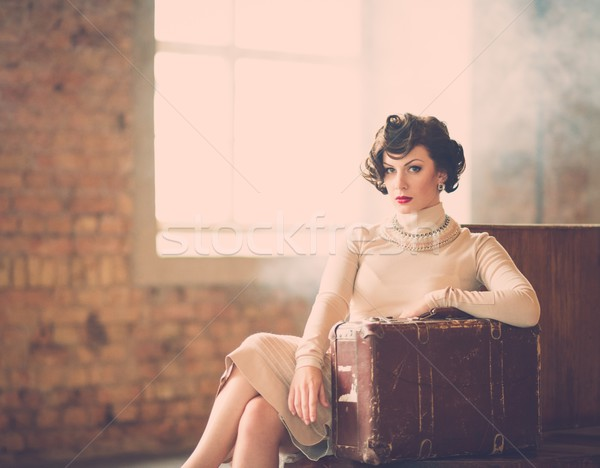 Beautiful vintage style young woman with suitcase on a train station Stock photo © Nejron