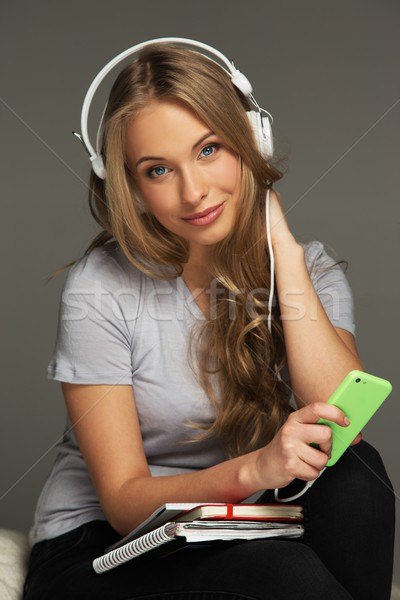 Positive woman student with notebook listens to music Stock photo © Nejron