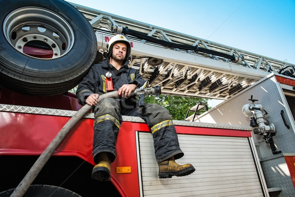 Firefighter sitting on a firefighting truck with water hose  Stock photo © Nejron