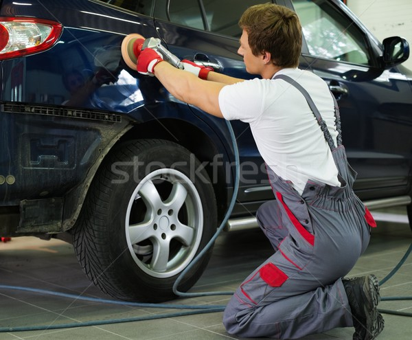 Serviceman polishing car body with machine  in a workshop Stock photo © Nejron