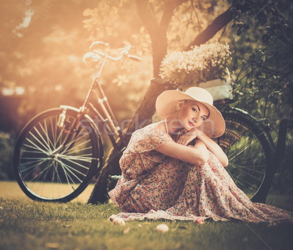 Beautiful blond retro woman with bicycle behind her Stock photo © Nejron