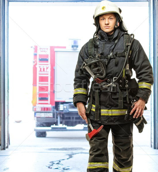 Young firefighter against truck in firefighting depot  Stock photo © Nejron