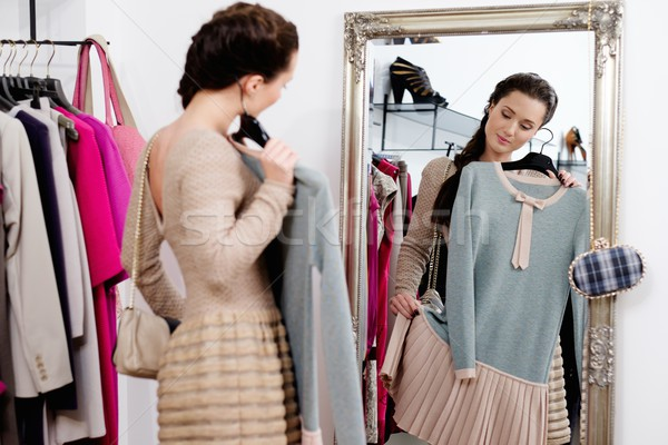 Young woman choosing clothes in a showroom  Stock photo © Nejron