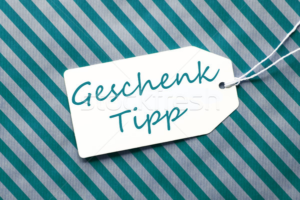 Label On Turquoise Wrapping Paper, Geschenk Tipp Means Gift Tip Stock photo © Nelosa