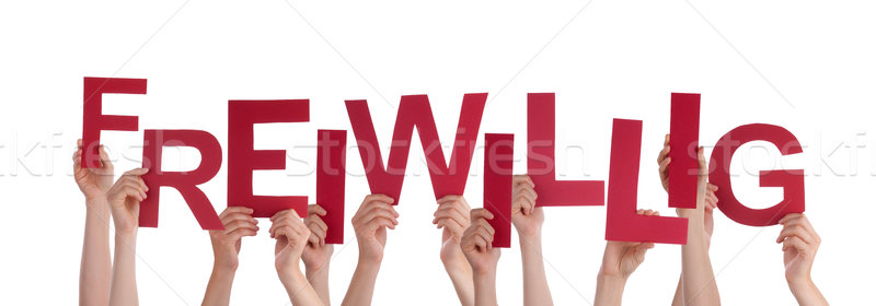 People Holding Red Word Freiwillig Means Voluntary Stock photo © Nelosa