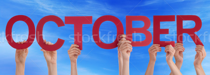 Stock photo: Many People Hands Holding Red Straight Word October Blue Sky