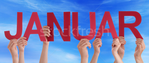 People Holding Straight German Word Januar Means January Blue Sk Stock photo © Nelosa