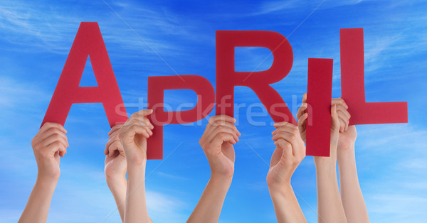 Stock photo: Many People Hands Holding Red Word April Blue Sky