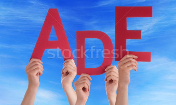 People Holding German Word Ade Means Goodbye Blue Sky Stock photo © Nelosa